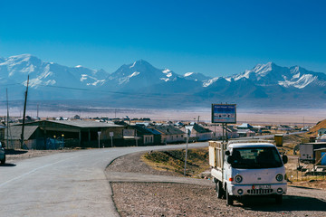 Car standing on the road with beautiful landscape of the Pamir mountains in South Kyrgyzstan on the background. The village of Sary-Mogul.