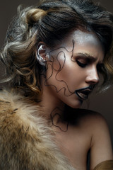 Beautiful girl with creative make-up with gold and silver and curls. Model with fur and bright dark lips. Beautiful face. The image in Gatsby style. The photo was taken in a studio.