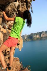 young woman rock climber climbing at seaside cliff