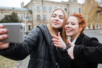 Teenagers taking selfie and showing thumbs up gesture outdoors