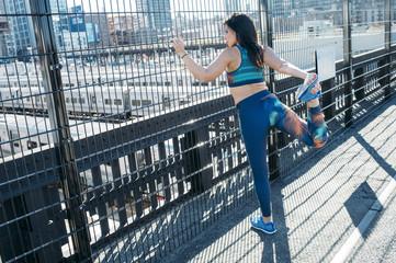 Woman stretching near fence