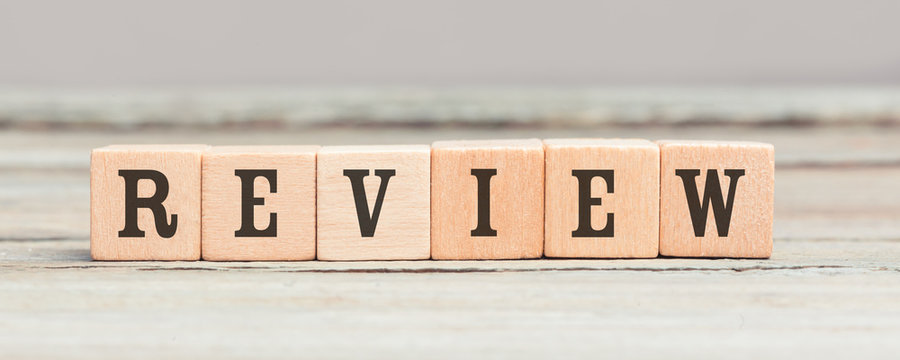 Word review written with wood cubes on table