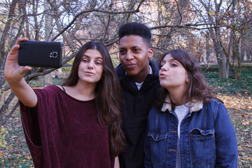 Group of young people, two caucasian girls and a black boy doing a selfie in the field with a cell phone. They are friends.
