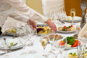 The waiter prepares for a banquet table