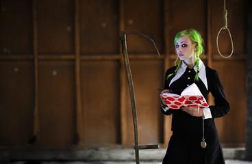Junge Frau in Gothic Schulmädchen Kostüm mit Sense