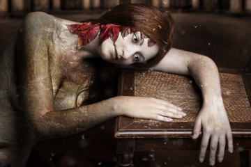 Mystisch, verträumtes Portrait einer jungen rothaarigen Frau an einem antiken Holzstuhl