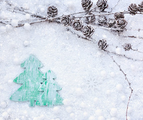 Larch branches with cones and christmas tree on the snow. Christmas background with space for your text.
