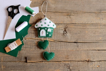 House made of felt and decorated with snowflakes and a metal key. House with hearts crafts, scissors, thread, felt sheets on wooden background with copy space for text. Beautiful wall decor. Top view