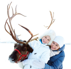 Happy little girl with mom hugging her reindeer. Winter playtime