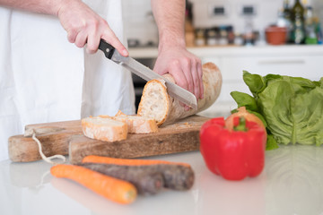 Man hands cutting bread slices in the kitchen , main focus on the bread