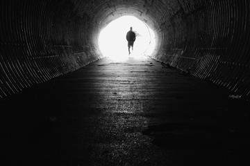 light at the end of the tunnel with silhouette of man