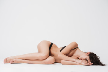 Woman in lingerie laying on a side with eyes closed
