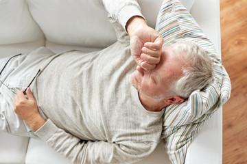 close up of tired senior man lying on sofa at home Wall mural