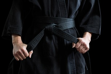 Confident karate player holding his belt