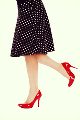 Vintage style shot of legs of sexy plus size woman in red stilettos and black polka dot skirt