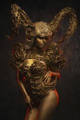 Beautiful devil women with golden ornamental horns on dark background