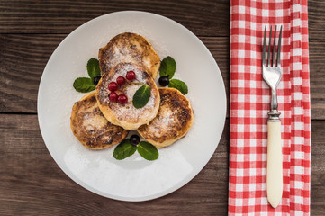 Cheesecakes with currants covered  powdered sugar on a wooden background. Top view