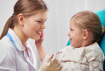 Smiling female dentist with little patient in dental clinic. Concept of yearly teeth examination.