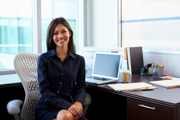 Portrait Of Female Doctor Sitting At Desk In Office