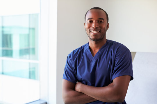 Portrait Of Male Nurse Wearing Scrubs In Exam Room