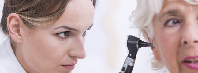Doctor checking patient's ear with otoscope