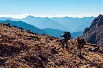 Hikers with Backpacks walking on grassy heel in Mountains