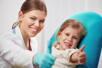 Happy child patient with woman doctor showing thumbs up in clinic. Health care concept.