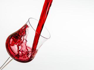 bicchiere di vetro con vino rosso che viene versato
