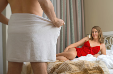 Man flirting with his girlfriend at hotel room.