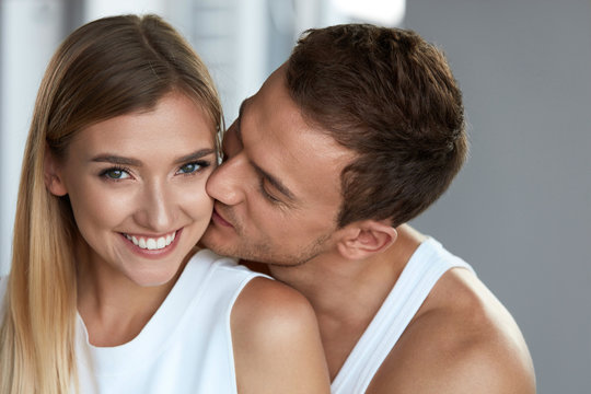 Portrait Of Handsome Man Kissing Happy Woman With Soft Face Skin