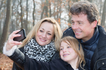 blond daughter make a selfie with mother and father parent in winter