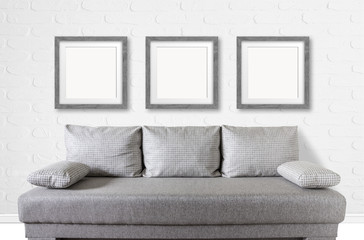Three blank  frames over modern couch at white bricks textured wall, interior decor mock up.