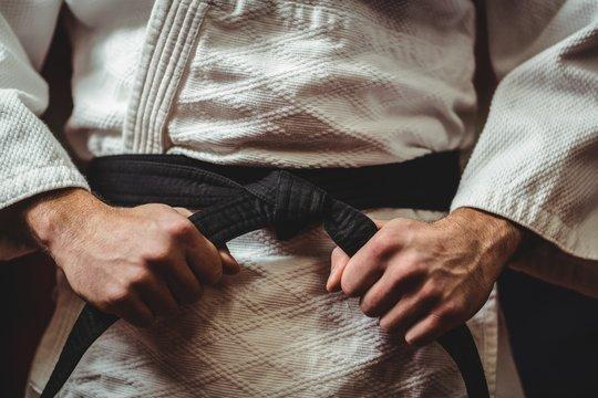 Karate player tying his belt