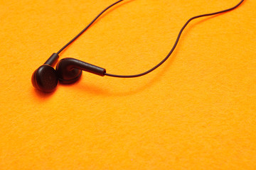 Earphones isolated against a yellow background