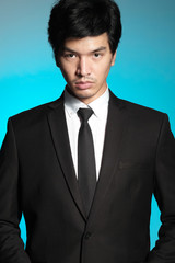 Asian man in black suit and white shirt on blue background