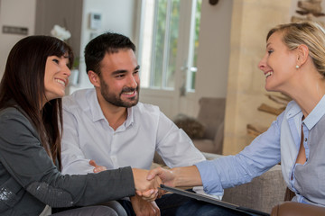 young Hispanic couple shaking hands with realtor