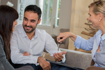 Woman Handing Over the House Keys to young couple