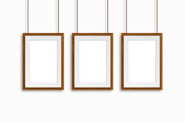 Three yellow wooden frames, hanging on cords, interior decoration idea