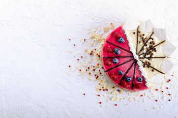 Delicious raspberry cake with fresh raspberries, blueberry, almond slices, rose pepper and chocolate cheesecake on white concrete background.