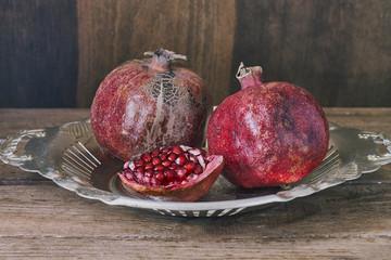 Ripe pomegranate fruit on wooden background.