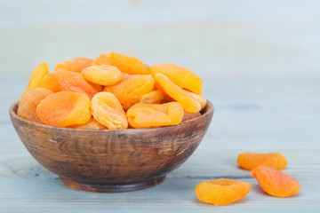 Delicious dried apricots in wooden bowl over blue background