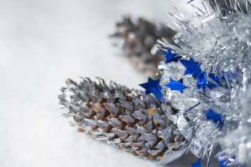 Christmas decoration - Silver and blue Christmas tinsel and pine cone on white background