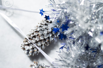Christmas decoration - Blue and silver Christmas tinsel and pine cone on white background