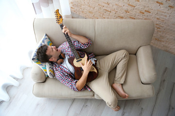 Young man with headphones playing guitar and lying on the sofa