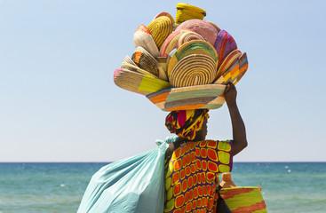 donna africana immigrata che vende cestini in Italia lungo la spiaggia