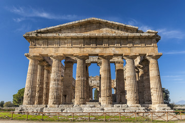 Front view of greek temple of Neptune, in the archaeological site of Paestum, Salerno, Italy