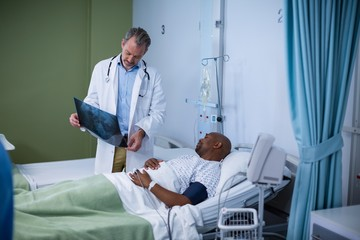 Doctor discussing x-ray with patient in ward