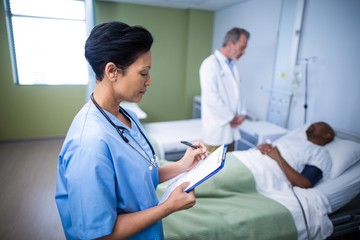 Female nurse writing on clipboard during visit in ward