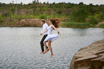 bride and groom jumping together into the water
