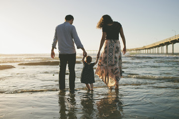 Rear view of parents holding daughter's hands while walking in sea during sunset